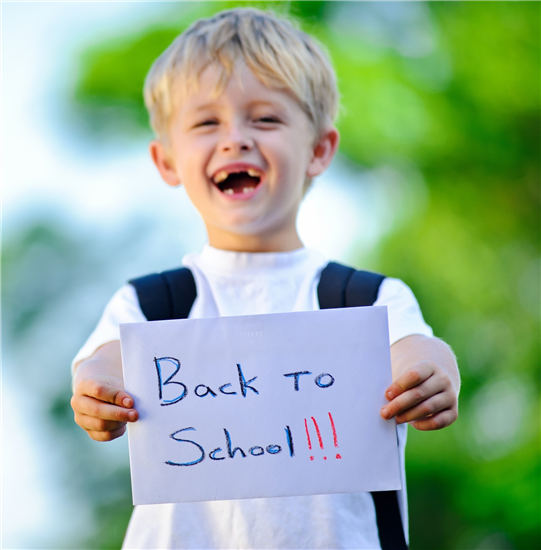 Young boy smiling and holding sign saying back to school